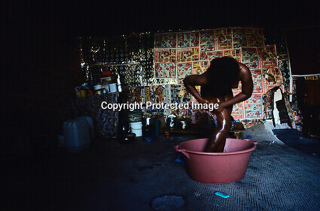 Bonginkosi Bauuma, age 15, washes her body in the family shack before going to school in Khayelitsha, the biggest black township outside Cape Town, South Africa. The family doesn't have electricity or running water. They heat water with paraffin stove. Her father works as a cleaner at a primary school, and the mother at a pre-school. It's estimated that over one million people live here, most of them under appalling conditions in shacks with no running water or electricity. (Photo by: Per-Anders Pettersson)