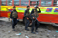 Indian Black Cats commandos walks next to a bus in front of The Taj Mahal hotel during the final gun battle between the Indian commandos and  militants inside the hotel in the early hours of 29th of November 2008 in Mumbai, India.