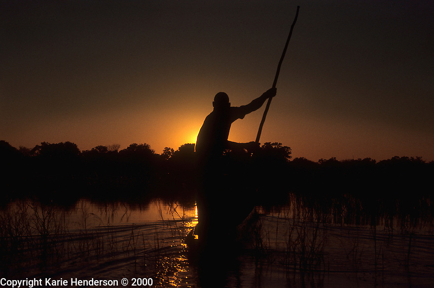 """Electricity"", a guide in the Okavango Delta, Botswana steers a mokoro, dugout boat, into the sunset. Photo by, Karie Henderson © 2000"