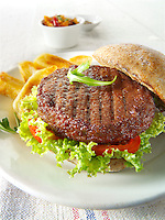 Beef burger in a wholemeal bun with salad and french fries photo. Funky Stock Photos