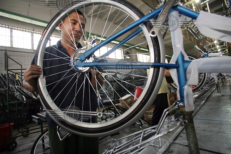 A worker fits a wheel onto a new bike on the assembly line at the Flying Pigeon bicycle factory.