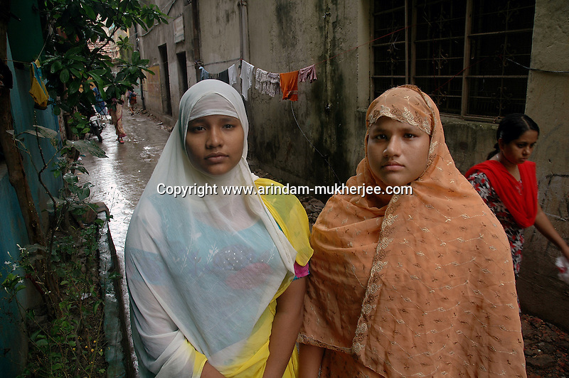 INDIA (West Bengal - Calcutta)July 2007,Shakila Babe(right) and Sanno Babe (left) in front of their house at Iqbalpur.  Shakila and Shanno are twins from a poor muslim family of Iqbalpur, Kolkata. . Inspite of their late father's unwillingness to send his daughters to take up  boxing her mother Banno Begum inspired them to take up boxing at the age of 3. Their father was more concerned about the social stigma they have in their community regarding women coming into sports or doing anything which may show disrespect to the religious emotions of his community. Shakila now has been recognised as one of the best young woman boxers of the country after she won the  international championship at Turkey in the junior category. Shanno is also been called for the National camp this year. Presently Shakila and Sanno has become the role model in the Iqbalpur area  and parents from muslim community of Iqbalpur have started showing interst in boxing. Iqbalpur is a poor muslim dominated area mostly covered with shanty town with all odds which comes along with poverty and lack of education. - Arindam Mukherjee