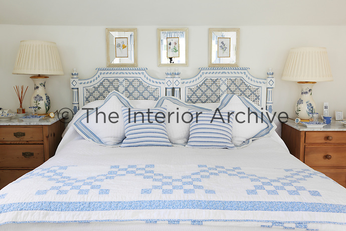 A bed dressed with a blue and white quilt and striped cushions