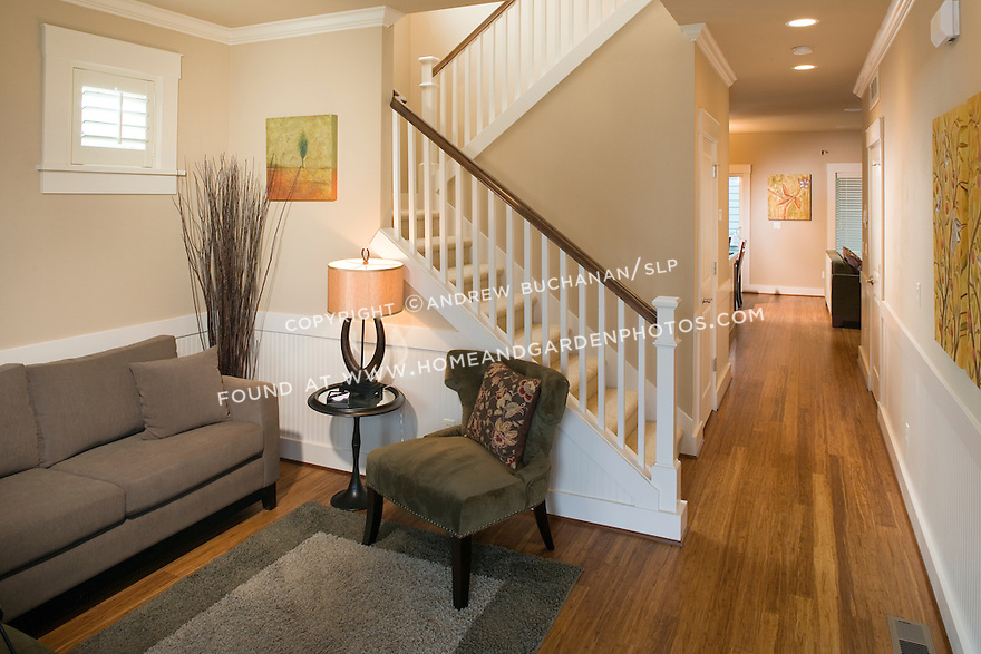 Looking through a front door at a modern day sitting room or entry parlor that makes good use of tight space in this townhouse-style builder spec home, while a u-shaped staircase winds up and a long entry hall hints at the warmth of the kitchen and family room area beyond.