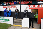 Two supporters wearing boiler suits against the cold and a security official on guard at the players tunnel at Bellslea Park, home of Fraserburgh FC, prior to the club's Highland League fixture against visitors Strathspey Thistle. Nicknamed 'The Broch,' Fraserburgh have been members of the Highland League since 1921 having been formed 11 years earlier. The match ended in a 2-2 draw in front of a crowd of 302.
