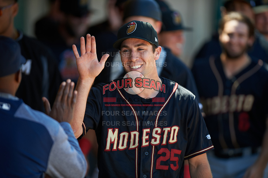 Modesto Nuts shortstop Johnny Adams (25) celebrates with teammates after pitching an inning of relief during a California League game against the Inland Empire 66ers on April 10, 2019 at San Manuel Stadium in San Bernardino, California. Inland Empire defeated Modesto 5-4 in 13 innings. (Zachary Lucy/Four Seam Images)