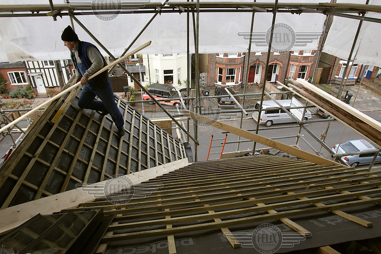 A Polish construction worker lays a roof on a housing renovation site.  Since Poland became a member of the EU (European Union) in 2004, thousands of Poles have arrived in the UK to work, as Britain is one of the very few countries to lift employment restrictions on immigrants from the new member states.