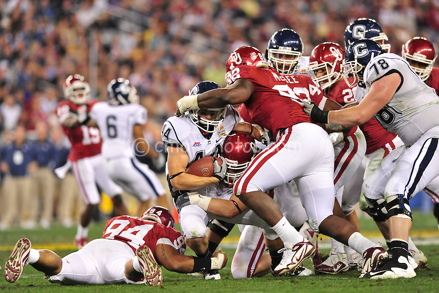 Jan 1, 2011; Glendale, AZ, USA; Connecticut Huskies running back Robbie Frey (44) is gang-tackled by the Oklahoma Sooners defense in the 3rd quarter of the 2011 Fiesta Bowl at University of Phoenix Stadium.  The Sooners won the game 48-20.