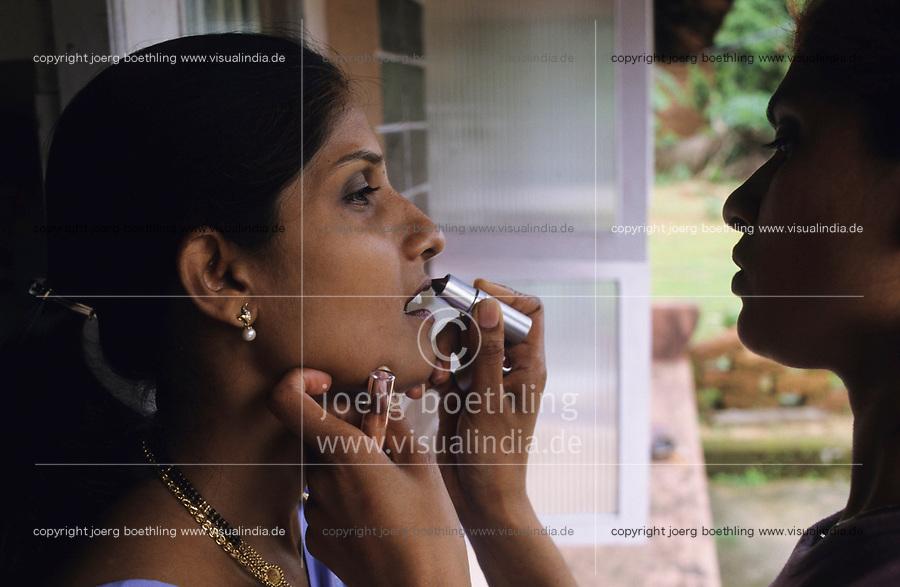 INDIA, Mangalore, woman apply lipstick