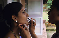 INDIA, Mangalore, woman apply lipstick