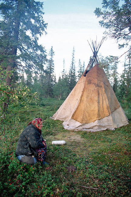 Anna Yurieva, a Sami woman from Lovozero, sits near her Lavo (tent) at a summer fishing camp. Kola Peninsula, NW Russia