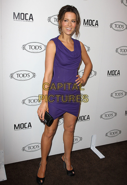 KATE BECKINSALE.Tod's Beverly Hills boutique Grand Opening held At Tod's Boutique, Beverly Hills, California, USA. .April 15th, 2010 .full length sleeveless purple ruched body con dress bodycon cowel neck hand on hip tanned black peep toe shoes clutch bag .CAP/ADM/KB.©Kevan Brooks/AdMedia/Capital Pictures.