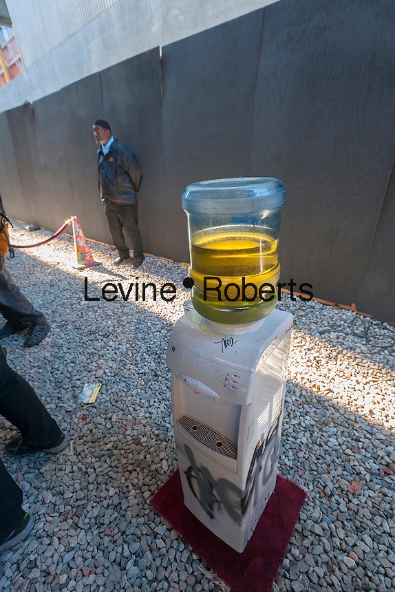 "A water dispenser serves ""refreshments"" in the trendy West Chelsea gallery district in New York on Friday, October 18, 2013 as part of the eighteenth installment of Banksy's graffiti art, a collaboration with the Brazilian artists, Os Gemeos. This installment is set up like a museum exhibit in an empty lot under the High Line Park complete with ""museum"" guards to handle crowd control. The elusive street artist is creating works around the city each day during the month of October.  (© Richard B. Levine)"
