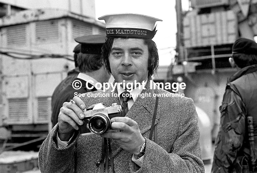 Cyril Cain, photographer, Daily Mirror, UK. Cyril was Belfast-based during much of the N Ireland Troubles. A native of the the Isle of Man he is seen wearing the cap of a crew member on board the prison ship, HMS Maidstone, moored in Belfast  197303020117a.<br />