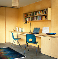 This home office is lined with plywood, a material which is both textural and different to normal wall coverings, and has a concrete floor with underfloor heating