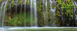 Water cascades down moss laden cliffs into the Sacramento River at a unique falls in Northern California. <br />