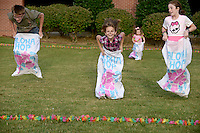 NWA Democrat-Gazette/BEN GOFF @NWABENGOFF<br /> Justin See (from left), 15, of Centerton, Hailah Birk, 8, of Centerton, Sophia Marcum, 3, of Rogers and McKenley Loan, 9, of Bentonville take part in a sack race on Thursday Sept. 24, 2015 during the annual Northwest Arkansas Community College Student Ambassador and Activities Board Welcome Back Luau at the school's Bentonville campus.