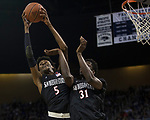 San Diego State guard Nisre Zouzoua (5) grabbs a rebound over teammate forward Nathan Mensah (31) against Nevada in the second half of an NCAA college basketball game in Reno, Nev., Saturday, March 9, 2019. (AP Photo/Tom R. Smedes)