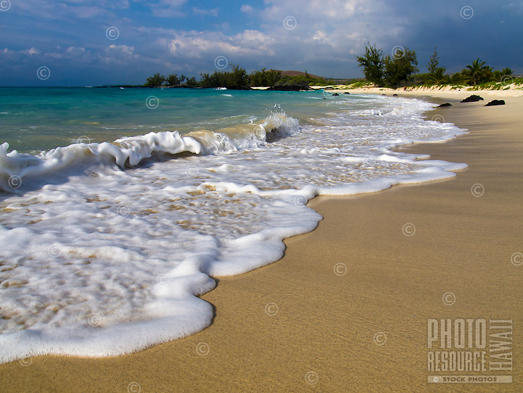 A wave curls at the shoreline of the Big Island's Makalawena beach on a sunny day.