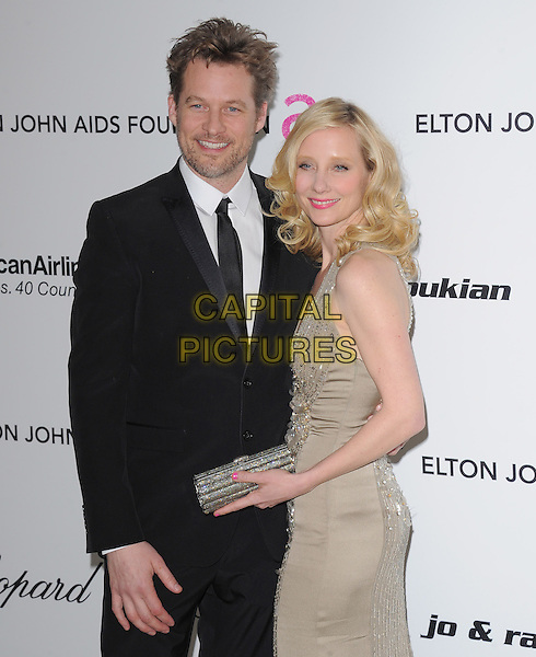 JAMES TUPPER & ANNE HECHE.19th Annual Elton John AIDS Foundation Academy Awards Viewing Party held at The Pacific Design Center, West Hollywood, California, USA..February 27th, 2011.half length gold dress sequins sequined  stubble facial hair black suit couple .CAP/RKE/DVS.©DVS/RockinExposures/Capital Pictures.