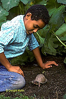1R14-015z Minority Child with Box Turtle in garden.