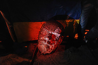 The shattered head of The Lenin statue is used like a trophy in front of a Ukrainian flag  by the outraged protesters in Kiev