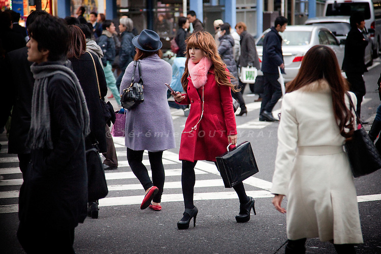Tokyo. A young japanses girl crossing in front of Shinjuku train station.