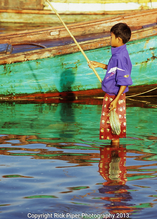 Cambodian Boy Fishing 02 - Young Cambodian boy fishing in the Sanke river at dawn, Kampot, Cambodia.