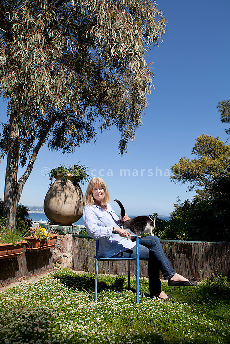 Sarah Bartlett, astrologer, poses for the photographer in her garden, Mandelieu-la-Napoule, France, 03 May 2012. She sits in this blue chair to meditate, facing the view across the sea to Cannes.