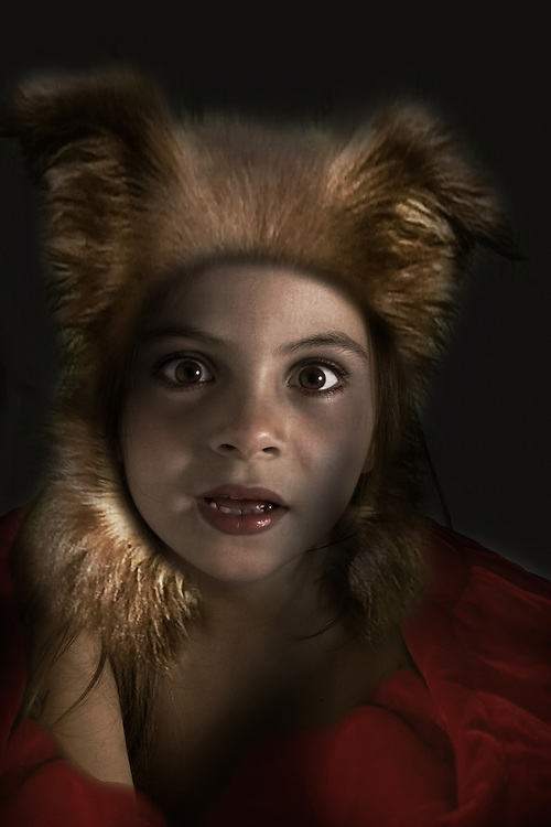 A young girl with wide eyes looking at the camera wearing red clothes and fur headwear