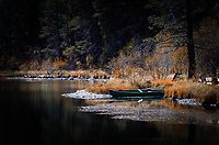A canoe sits on the bank of the Truckee River on a late fall day.  The river is at its lowest level of the year.