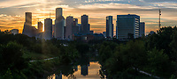 Golden Skyline Over Buffalo Bayou Pano -  Houston skyline over Buffalo Bayou at sunrise just as the the golden glow of the sun rays pops through the high rise buildings in this pano on this early morning. The bayou in the city runs from Katy Texas east through Houston about 53 miles through the city and to the ship channel and out in the gulf of mexico. At one time the bayou were not so welcoming a place but the city cleaned it up and added several parks along the water and now it is a very popular place to visit as they have added hike and bike routes, skate parks, volley ball and many other new feature in the parks to make it more attactive place to visit. Also they hold concerts and other events here through out the year.