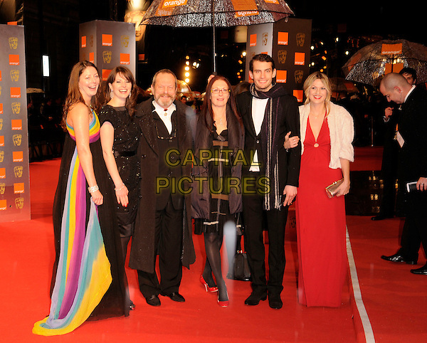 TERRY GILLIAM & GUESTS .The Orange British Academy Film Awards 2009, Royal Opera House, Covent Garden, London, England, February 8th 2009..BAFTAS arrivals full length black suit scarf tie dress umbrella raining  .CAP/FIN.©Steve Finn/Capital Pictures