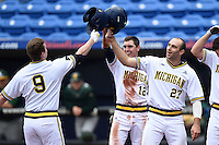Michigan Wolverines Jackson Glines (27) and Eric Jacobson (12) congratulate Travis Maezes (9) after hitting a home run during the first game of a doubleheader against the Siena Saints on February 27, 2015 at Tradition Field in St. Lucie, Florida.  Michigan defeated Siena 6-2.  (Mike Janes/Four Seam Images)
