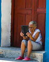 A woman uses a tablet to chat on the internet with relatives at a Wifi hotspot in Regla, Havana, Cuba, Monday, March 27, 2017. Cuba is one of the world´s least connected countries in the world and just over the last couple of years internet access is spreading for the population with public wifi hotspots in every town´s main park.