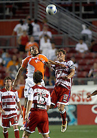 Houston Dynamo's Dwayne De Rosario (24) and FC Dallas' Simo Valakari (17) battle for a header at Robertson Stadium in Houston, TX on Saturday May 6, 2006. The Houston Dynamo defeated FC Dallas 4-3.