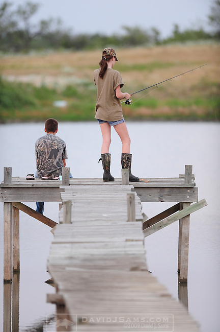 FISHING POND..Girl and Boy age 13-14 fish for bluegill and catfish on  farm pond near Waco Texas