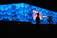 A guard walks in front of the The Beijing National Aquatics Center. Also known as the Water Cube it was built alongside Beijing National Stadium in the Olympic Green for the swimming competitions of the 2008 Summer Olympics. Following the Olympics, half the interior was turned into a water park..