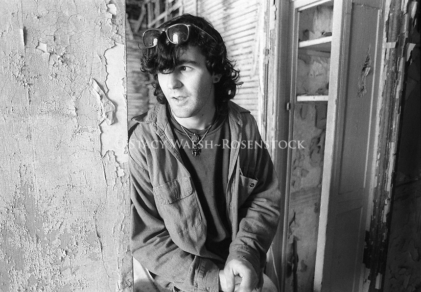 """New York, NY 1 May 87 - """"John Squat"""" in his East Village Squat, in an abandoned tenement building on East 8th Street. The building had no heat, water, or even a staircase to access floors so some of the squatters installed a ladder to climb from one floor to another."""