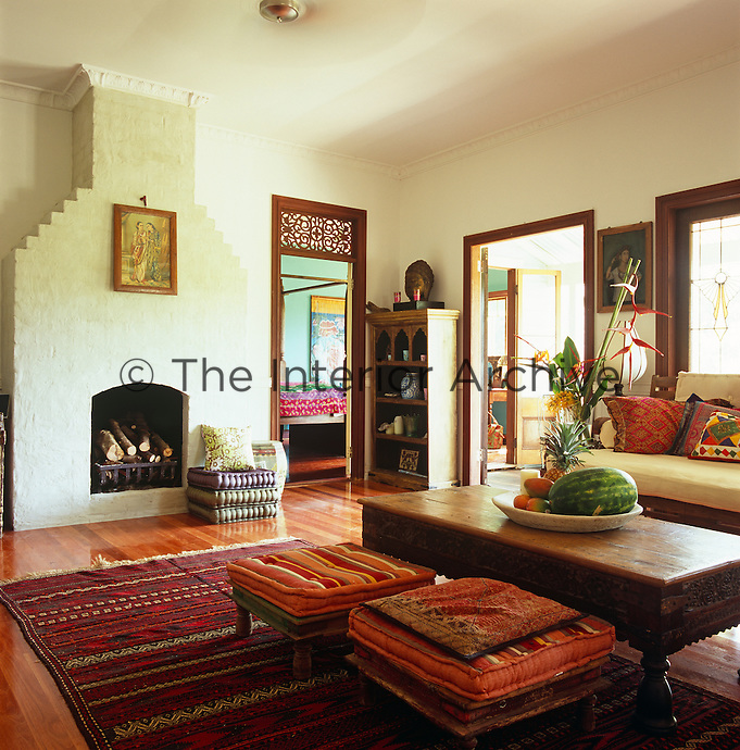 The living room is furnished with an Indian table, sofa and stools with a colourful rug on the polished wooden floor