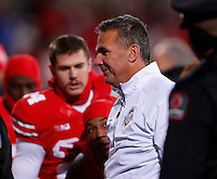Ohio State Buckeyes head coach Urban Meyer is escorted off the field by security following a 42-14 win over Indiana in Saturday's NCAA Division I football game at Ohio Stadium in Columbus on November 23, 2013. (Barbara J. Perenic/The Columbus Dispatch)
