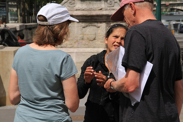 Woman performing the Gold Ring scam on tourist couple, Paris, France. .  John offers private photo tours in Denver, Boulder and throughout Colorado, USA.  Year-round. .  John offers private photo tours in Denver, Boulder and throughout Colorado. Year-round.