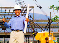 Man wearing hard hat holding architectural plans at construction site.