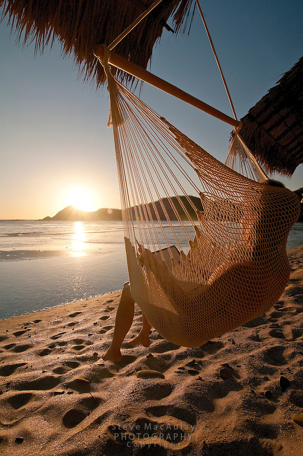Young woman relaxing in swinging hammock chair on sea shore as sun sets behind, Morgan's Rock Hacienda and Eco Lodge, Nicaragua