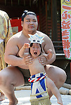 "April 29, 2016, Tokyo, Japan - A baby held by a sumo wrestler cries during the ""Nakizumo"" or ""baby-cry sumo"" competition at the Yukigaya-hachiman shrine in Tokyo on Friday, April 29, 2016. Japanese parents believe that sumo wrestlers can help make babies cry out a wish to grow up with a good health. (Photo by Yoshio Tsunoda/AFLO) LWX -ytd-"