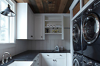 A white clapboard utility room houses a bank of modern washing machines and driers