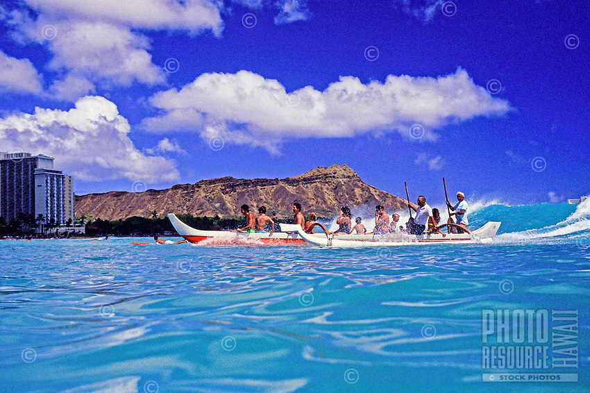Great shot of two outrigger canoes filled with happy tourists coasting on a perfect wave toward the shore of Waikiki Beach. Full length shot of Diamond Head in the background with puffy white clouds set against a brillliant blue sky.