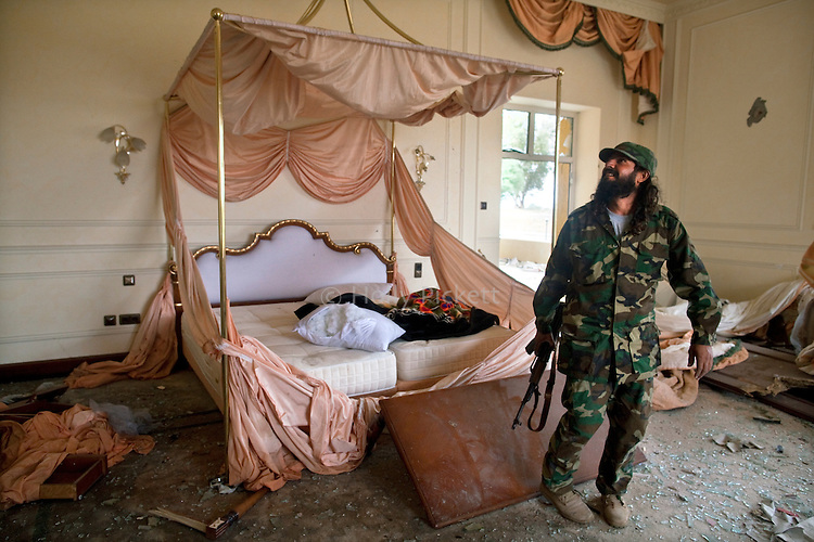A revolutionary fighter took in an expansive bedroom in a bombed and looted Gaddafi family palace in Sirte, Libya, Oct. 10, 2011.