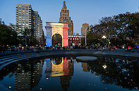 New York, NY - 15 November 2015 NYC  The arch in Washington Square Park lights up in solidarity with Paris.  Beneath the arch is a candlelight shrine to commemorate the victims of the 13 November Paris terror attacks.