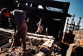 Tieling city, Liaoning Province, China, 11-2003..Demolition workers take down a disused factory in China's northeastern rustbelt. Millions of workers have been laid-off as China restructures its economy, slashing the bloated state-sector economy..